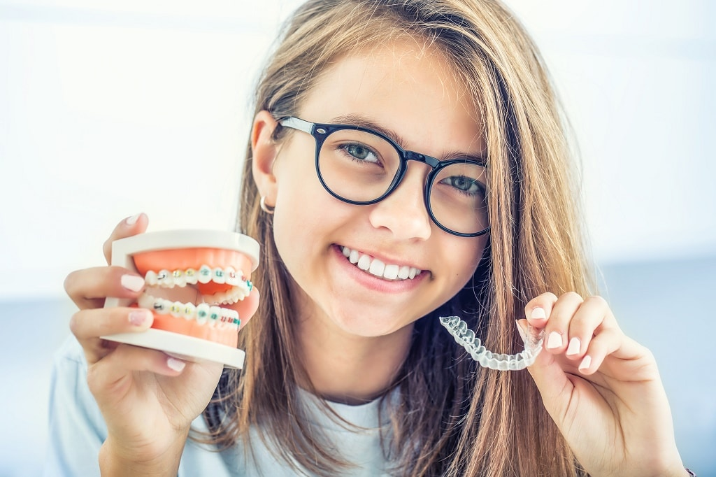 A teen aged girl wearing glasses and holding up a model of traditional braces and Invisalign clear aligners